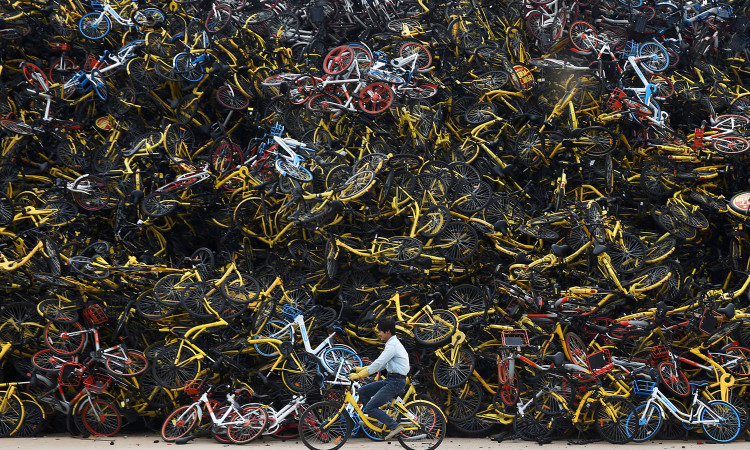A worker rides a shared bicycle past piled-up shared bikes at a vacant lot in Xiamen, Fujian province, China December 13, 2017. Picture taken December 13, 2017. REUTERS/Stringer  ATTENTION EDITORS - THIS IMAGE WAS PROVIDED BY A THIRD PARTY. CHINA OUT.     TPX IMAGES OF THE DAY - RC16B19B1FA0